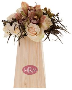 With the continued popularity of neutral hues in 2015 weddings, you're sure to see the addition of sophisticated Marsala. Personalized with a color-coordinated monogram and nestled into a bamboo printed vase, the bridal bouquet quickly displays and becomes a lovely addition to the bridal table.