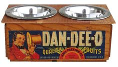 Unique eco-friendly repurposed genuine vintage Dan-Dee-O wooden fruit crate feeding station. Charming pine fruit box is configured for a small pet table with stationary top with no storage.  Beautiful original graphic of a jaunty gentleman with top hat and cane.