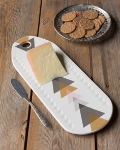 Arrow Cheeseboard - Delight guests with a ceramic cheese board, featuring a geometric design in soft pastels and golden metallic. When not in use, the board can be hung as a display piece. Soft Pastels, Arrow, Coasters, Metallic, Display, Cheese, Ceramics, Mugs, Board