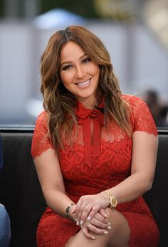Adrienne_Bailon smiling in tomato lace pencil dress w/ chestlength mid-brown hair