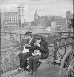 London, 1943: Lilian Carpenter (left) and Vera Perkins eat their packed lunch on the back of their horse-drawn LMS Railway Company van. The area behind them has been badly damaged in an air raid.