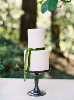 Simplistic two tier white wedding cake with sage green ribbon: http://www.stylemepretty.com/2016/08/30/sinclaire-moore-workshop-with-omalley-photographers/ Photography: O'Malley Photographers - http://omalleyphotographers.com/