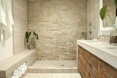 Zen bathroom features open shower clad in stone surround as well as stone shower bench accented ...