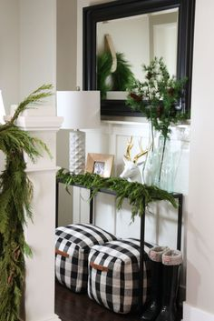 Christmas entryway table with buffalo check poufs and fresh garland - Life On Virginia Street