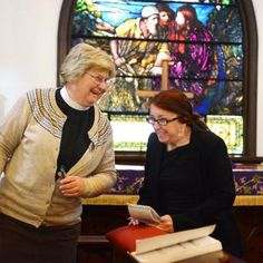 Register photo/LUKE WARK Minister Mary Staley, left and Sandusky Register reporter Melissa Topey share a laugh as Staley gives Topey a quick lesson in reading a prayer prior to the Sunday service at St. Paul's Episcopal Church on South Bass Island.