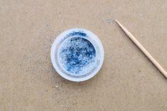 Mix glitter in bottle cap with toothpick