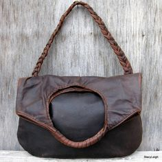Rugged, distressed, cowhide leather that looks like it has been someones favorite bag but it is brand new. The leather has a great broke in look and feel. Made to distress. It is what they call a pull up leather meaning a leather that lightens in color when stretched or scuffed. Tanned with some oils and waxes. Use as a tote or a shoulder bag. The inside is lined with matching leather and a faux snakeskin leather fabric. It has two drop in pockets inside plus a small one for cards. Magnetic…