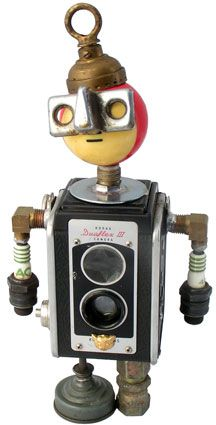 "Name: He-Boo  D.O.B.: 12/12/08  Height: 12""  Principal Components: Box camera, pool ball, spark plugs, lamp part, oil can, hydraulic fittings"