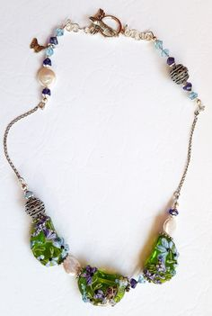 """Walking Through The Fairys Garden Hand-crafted Necklace. In spring we watch the flowers climb from their long sleep perhaps with some magical help. Let's all take a walk through """"The Fairy's Garden"""" as she peeks from behind blooms. Saskia McKenzie's lampwork even brought the fairy's delicate wings into a 3-D effect. Helping the colors glow are coin pearls, Swarovski crystals, and Bali Silver beads, suspended from a dainty sterling silver chain. The necklace measures 17 ¾ """" around one's neck."""