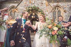 Orange wedding confetti photograph at Lulworth Castle church wedding.Photography by one thousand words wedding photographers