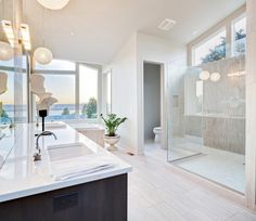 Bright and airy bathroom withe extensive windows, white design offset with dark vanity