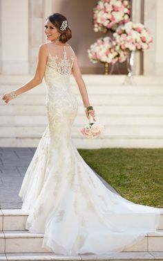 This modified fit and flare designer wedding dress by Stella York features an illusion neckline, sweetheart bodice and romantic lace embroidery throughout. The back zips up under fabric-covered buttons.