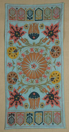Silk embroidery on cotton. Silk chain stitch in apricot, rose, dark blue, gold and green on a light blue ground.