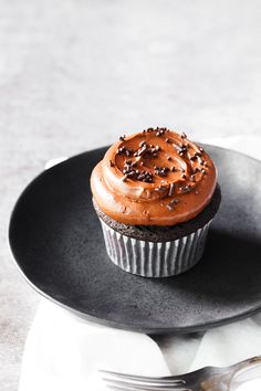 Chocolate cupcake frosted with chocolate frosting and chocolate sprinkles on a plate.