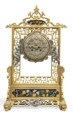 A FRENCH 'Japonisme' GILT AND SILVERED BRONZE CLOISONNE ENAMEL MANTEL CLOCK AND  POSSIBLY DESIGNED BY EMILE-Auguste REIBER FOR THE STAIRS CRYSTAL, PARIS, THIRD QUARTER 19TH CENTURY  CASE: the pierced frame in the form of a screen, applied with three ho -ho birds and set with enamelled reserved depicting flowers and butterflies against a black ground, supported on cast-mythical beast feet DIAL: with Japanese numerals and an engraved gilt hand Modelled as a dragon MOVEMENT