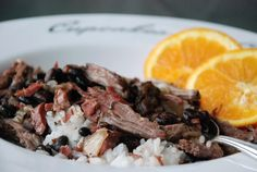 Brazilian Feijoada - pork butt [Boston Butt], beef short ribs, smoked ham hock, chicken broth, black beans, rice and orange slices are the main ingredients.