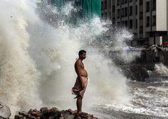 Mieszkaniec Bombaju stoi na brzegu Morza Arabskiego. Lipiec to w Indiach szczyt pory monsunowej