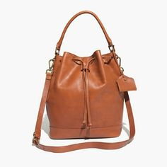 """NWT Madewell Lafayette Bucket Bag Madewell Lafayette Bucket Bag in english saddle color. This bag is NEW with tags still attached. Only visible flaw is shown I'm picture.  ?Genuine Leather ?Drawstring closure ?Fully lined interior ?3 interior side pockets ? 11 1/5"""" H ? 15"""" W ? 8 7/10"""" D Madewell Bags Crossbody Bags"""