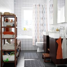 A bathroom with white wall tiles, grey floor tiles and two black-brown washbasin cabinets. Combined with two wall cabinets with mirror doors and dark brown shelving units.