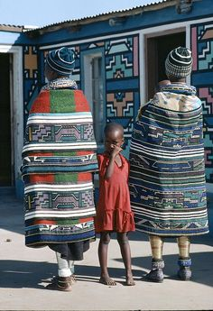 Ndebele mothers of South Africa show off the bold patterns of their traditional blankets.
