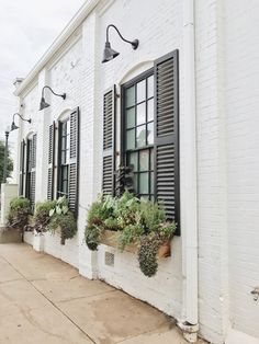 Outside of Magnolia Bakery.Beautiful idea for black shutters and window boxes on a brick house for curb appeal. Outdoor Barn Lighting, Exterior Lighting, Farmhouse Lighting, Farmhouse Windows, Farmhouse Shutters, Rustic Shutters, Repurposed Shutters, Diy Shutters, Window Shutters Exterior