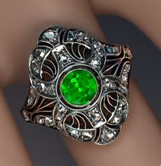 Art Deco Russian Demantoid Ring, Moscow, circa 1930. An elaborate openwork silver and gold ring features a very fine vivid green Russian demantoid garnet in a surrounding of 34 rose cut diamonds.
