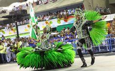 Ornando caveiras na fantasia, mestre-sala e porta-bandeira da Mocidade Independente de Padre Miguel sorriem durante performance