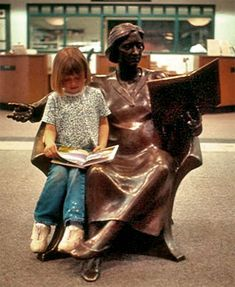 'Come Read With Me' - life-size bronze statue by Tuck Langland at a library in Goshen, Indiana.