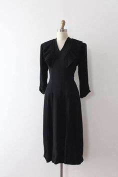 FOGA label designer Samuel Kass black rayon crepe dress from the 1940s. This dress features fun details throughout, a fitted waistline, and a lovely silhouette. Label: Original Samuel Kass Registered with FOGA