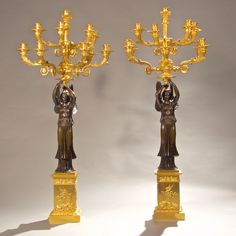 A pair of empire ormolu and patinated bronze figural ten light candelabra