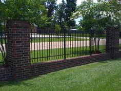 Wrought iron fencing with brick border.