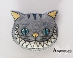 Broche inspirado en el gato de Cheshire, de Alicia en el País de las Maravillas (Tim Burton). Está confeccionado con fieltro e hilo, y relleno de algodón para hacerlo más blandito y agradable al tacto. A su vez, está decorado con lentejuelas y numerosos detalles bordados a mano. Precio: 5€