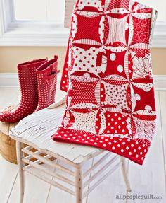 """Fifty-six red-and-white blocks create intersecting light and dark """"dots""""  in this throw. A polka dot border ties them together."""