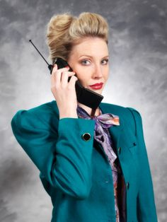 hair, phone, shoulder pads, bow shirt, all is so 80s business power woman