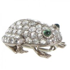 An 18ct white gold brooch made as a stylised frog crouched down on all four feet with rose cut diamonds grain set all over the arched back and rear legs totaling 0.92ct all highlighted with cabochon emerald eyes and four bright polished feet fitted to the reverse with a brooch pin. #Rutherford #Melbourne