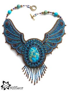 An elaborate bead embroidered necklace made with a blue sediment jasper cabochon, but it looks like it has bat wings!