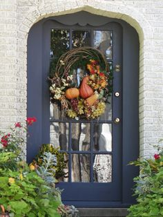 Clever curved frame adds more interest and curb appeal to this cottage door that features a Thanksgiving wreath.