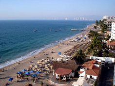 Los Muertos Beach, Puerto Vallarta, Mexico along the south end of the Malecon in downtown Puerto Vallarta. The marina is near the tall buildings in the background.