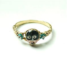 18th Century  Fantasie Mask Ring;    Gold ring, circa 1760, the twisted hoop decorated with turquoise enamel and diamond pansies symbolising pensee, [think of the giver]. The shank supports an oval bezel enamelled with a masked female face, with rose diamond eyes and garnet lips.