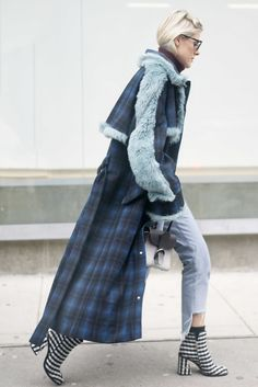 A printed coat paired with cut-out jeans and ankle boots.