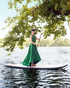 Amy Fine Collins, in a dress by Stacey Bendet for Alice + Olivia, paddleboarding on a pond near her home on Fishers Island in the Long Island Sound.