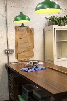 Decora Rosenbaum Temporada 1 - Alfaiataria. Mesa de cortes com pendentes verde e moldes. Foto: Felipe Felco Valle