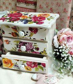 un petit meuble de rangement peint en blanc et décorée de papier decopatch à magnifiques motifs floraux