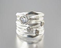 Diese Sterlingsilber blendet genial gewellte Ring in prächtigen Stil. Sechs gewellte Ringe sind aus einem Stück, so dass die Illusion der vielfachen stapelbar Ringe gestapelt. Sie sind mit vier akzentuiert funkelnd facettierten Zirkonia Steinen Lünette eingestellt wie Diamanten für maximale Brillanz. Die Steine liegt oben auf den Stapel mit der größeren einer Sitzung auf einem gehämmert strukturierte Ring einen schönen organischen Kontrast zu schaffen. Dieser schicke Aussage Ring der…