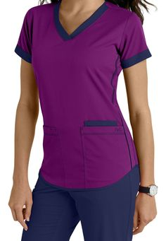 NrG by Barco brings to you this cute scrub top highlighted by contrast banded sleeves, neck and piping details on sides and hem. V-neck Three pockets Fitted back Contrast details Medium center back length 26 Vet Scrubs, Doctor Scrubs, Medical Scrubs, Scrubs Outfit, Scrubs Uniform, Jaanuu Scrubs, Scrubs Pattern, Medical Uniforms, Womens Scrubs