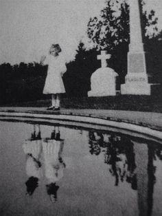 Creepy little girl with imaginary friend in pond reflection. Great picture to print out and frame for Halloween!