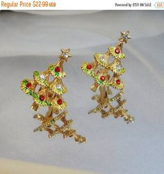 These #vintage Christmas earrings are just beautiful and sparkly!  They feature gold tone Christmas trees filled with red and clear rhinestones with hints of bright green en... #ecochic #etsy #jewelry #jewellery #holiday2014etfs