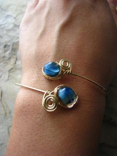 Gold Bangle Cuff with Blue Lampwork Wire Wrapped. $40.00, via Etsy.