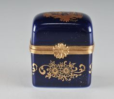 A pretty Limoges hinged box in cobalt blue with 22K gold transferred floral design to the sides and a courting couple motif to the top. The clasp has a daisy design, made in France.