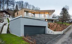 House On Steep Slope | Storey Home on Steep Slope with Grass Roofed Garage